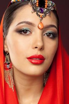 Красивая женщина в восточном стиле с мехенди на темном