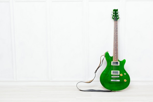 白い壁の背景の前に立てかけられたギター
