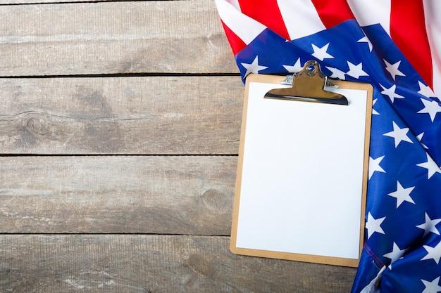空白のクリップボードと木製の背景にアメリカ国旗