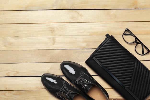 女性の靴と木製の背景のアクセサリー