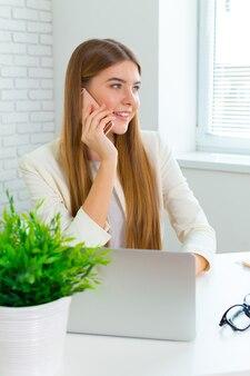 オフィスで彼女の職場に座って、電話で話している実業家の笑みを浮かべてください。