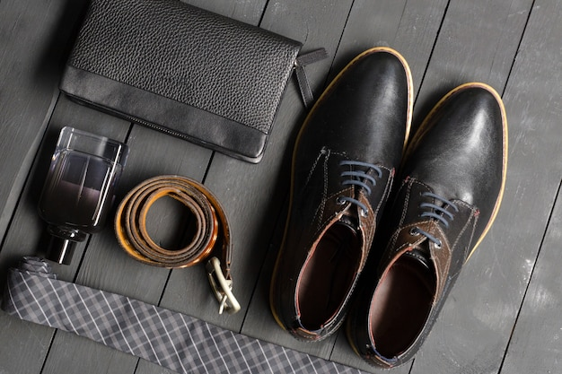 男性用の靴とアクセサリーは木製の床に置かれています
