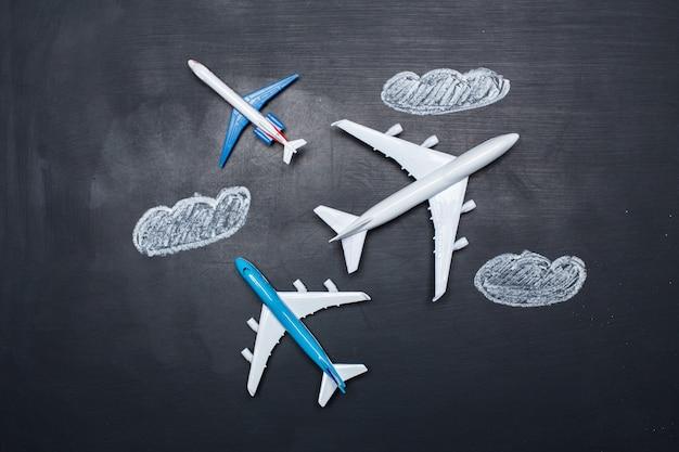 黒板と矢印の図面上のおもちゃの飛行機