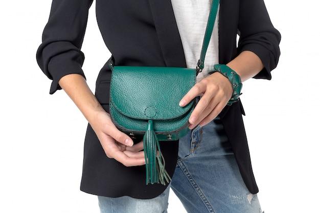 白で隔離されるハンドバッグを保持している女性
