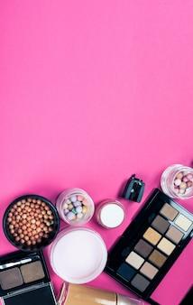 ピンクのテーブルにカラフルな化粧品のセット