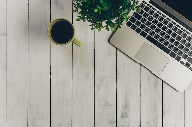 アクセサリーと近代的なオフィスのヴィンテージの木製デスクトップ上のラップトップ