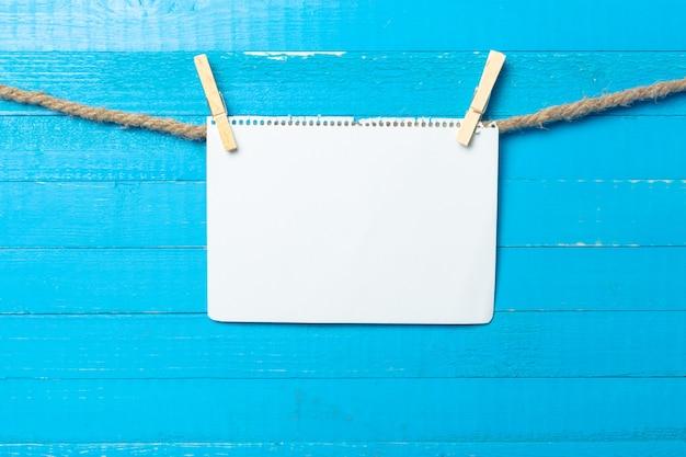 木製の背景に空白の紙で掛かっている洗濯はさみ