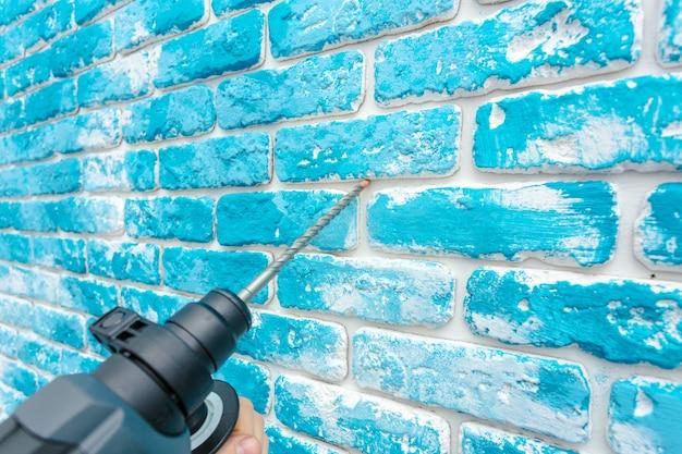 ハンマードリルを使用して壁に穴を開けます