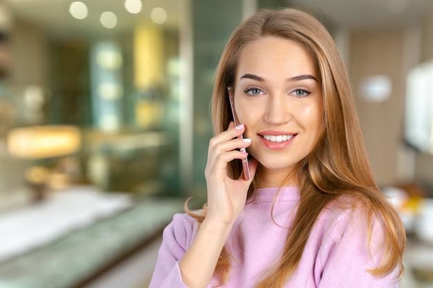 携帯電話で笑顔の若い女性