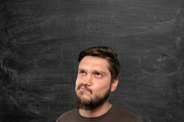 思慮深い表情でカジュアルな白人の若い男