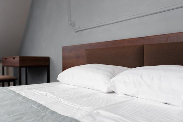 きれいな白い枕と美容室のベッドシーツを備えたベッドメイド。