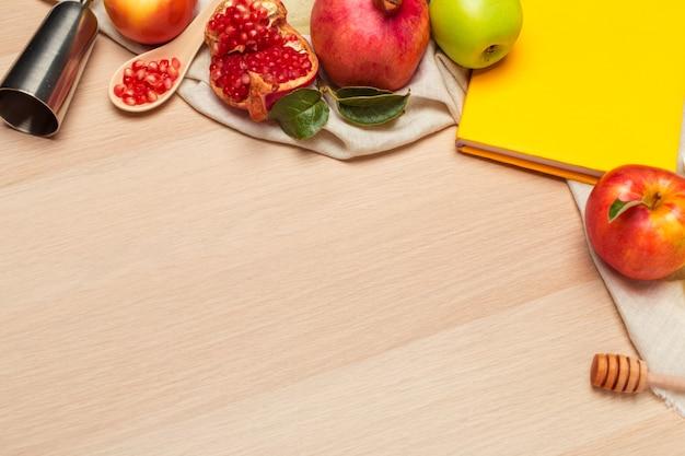 木の板にユダヤ人の新年の赤いリンゴ、ザクロ、蜂蜜の瓶