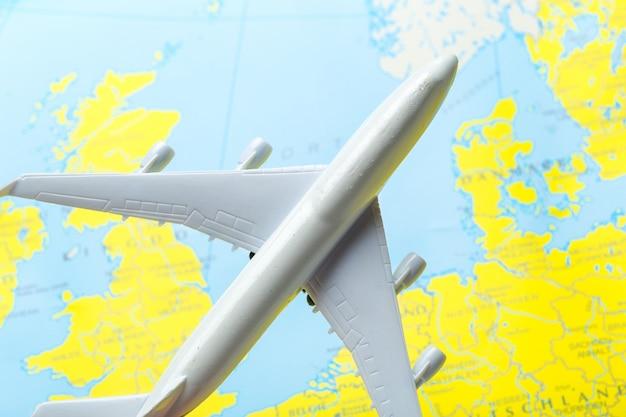 地図上を飛ぶ旅客機のミニチュア