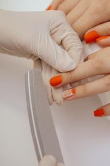 Маникюрник разглаживает ногти клиентов пилочкой
