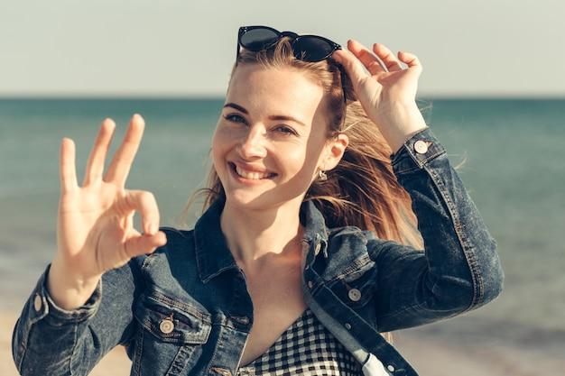 美しい若い女性は、ビーチで夏休みを楽しむ