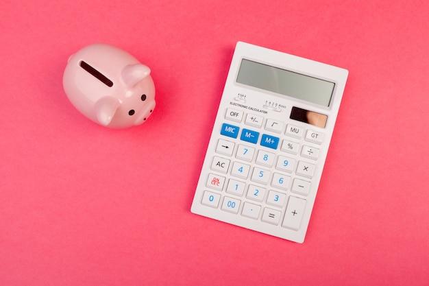 Копилка и калькулятор на предпосылке цвета, взгляд сверху.