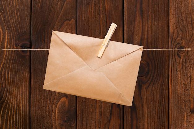 Пустой конверт висит на веревке на деревянной прищепке