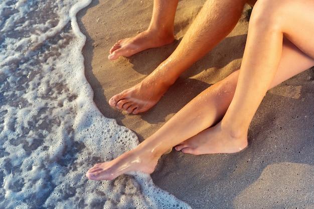 休暇の休日。ビーチで男性と女性の足のクローズアップ。