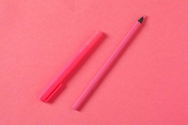 На розовом фоне школьные принадлежности и ручка, цветные карандаши