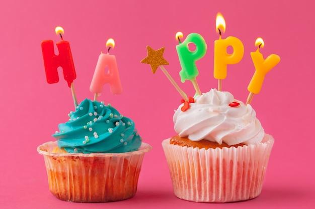 色付きの背景にキャンドルでおいしいカップケーキ。お祭りの背景、誕生日