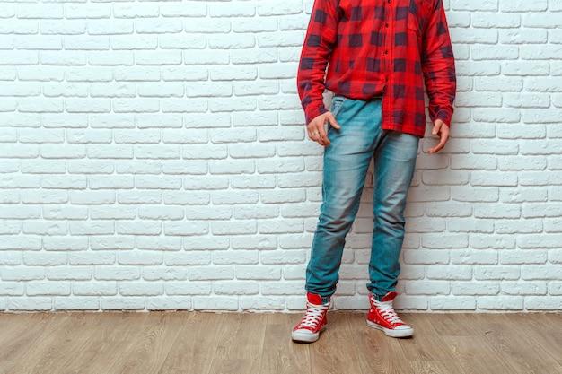 Ноги молодого человека моды в джинсах и кроссовках на деревянном полу