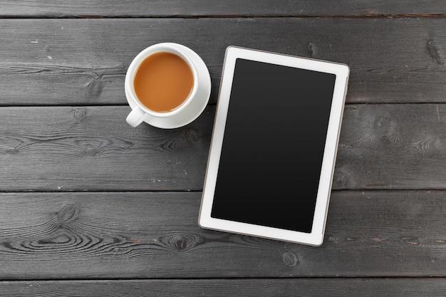 Цифровой планшет на деревянный стол в кафе с чашкой кофе