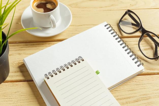 上面図。コーヒーとコーヒーカップ。空白のノートブックに置くペン。