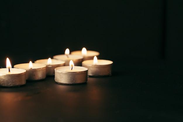 夜に燃える多くのキャンドル。暗い背景に輝く多くのろうそくの炎