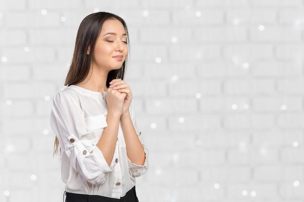 祈っている若い女性のクローズアップの肖像画