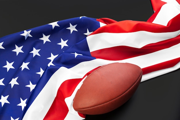 アメリカンフットボールボールとテーブルの上のアメリカの旗をクローズアップ