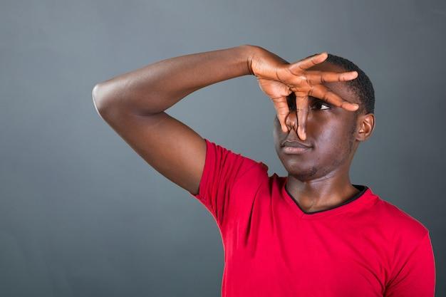 何か臭いので鼻を閉じるハンサムなアフリカ人のクローズアップの肖像画