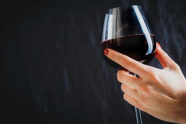 Рука бокал красного вина на темно-сером фоне