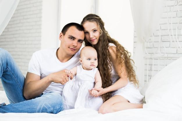 母と父はベッドで小さな赤ちゃんと
