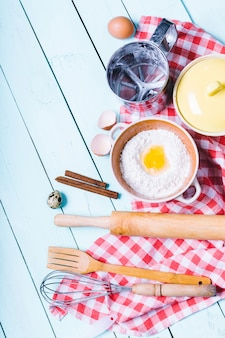 生地の準備。生地の材料-卵と小麦粉を麺棒で。木製の背景に。
