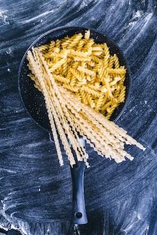 黒い木製の背景、上面に生スパゲッティ