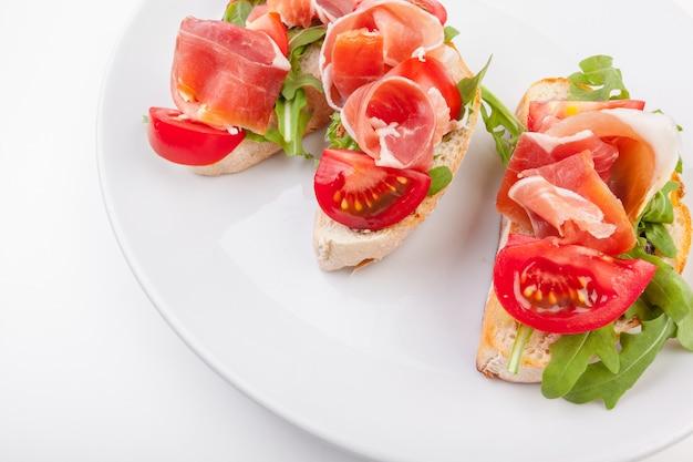 ハモン。タパスとして役立ったスペインセラーノハムとパンのスライス。生ハム、スペインの前菜。白い背景で隔離の生ハム