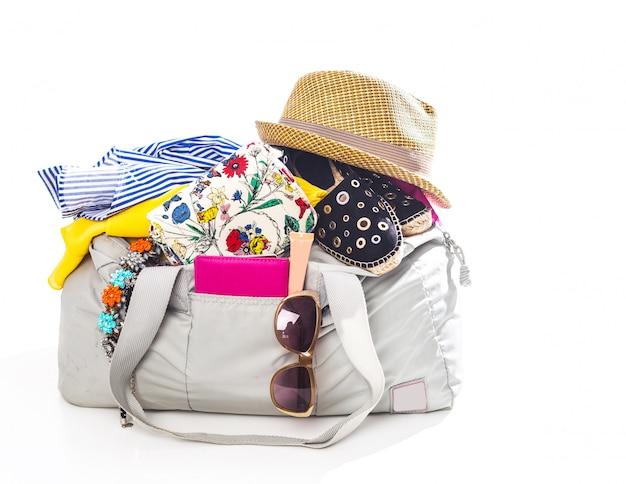 Упаковка чемодана для поездки на белом