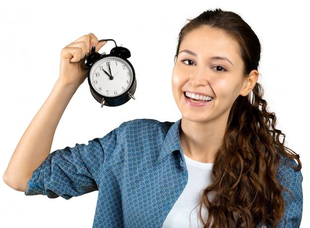 目覚まし時計を保持している若い女性