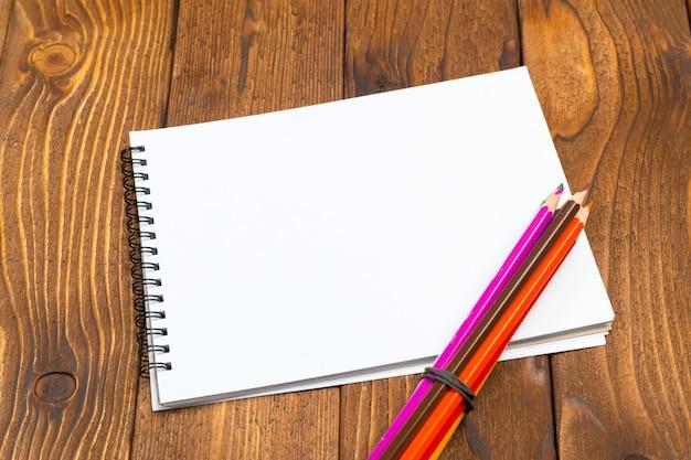空白の紙と木製のテーブルの上のペン