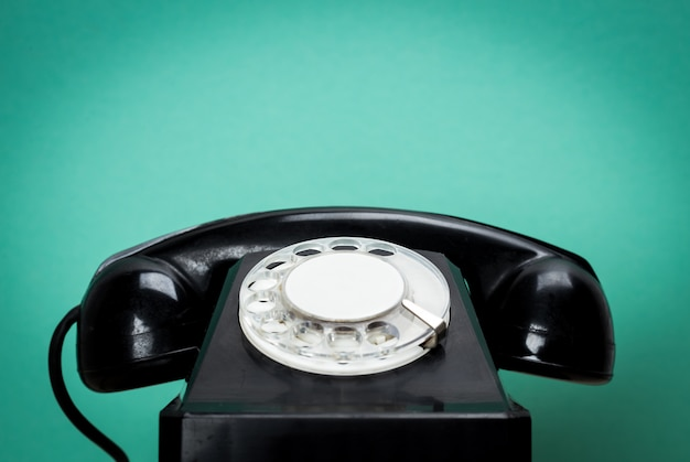 古いスタイルの背景の木のテーブルにレトロな電話