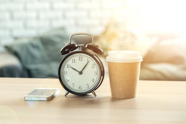 木製の背景に古典的なビンテージ目覚まし時計とコーヒーカップ