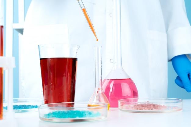 Манипуляции с лабораторными стеклянными химическими контейнерами на столе