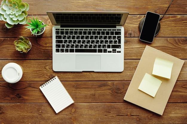 オフィステーブルワークスペーストップビュー。ラップトップ、デバイス、プラント付きの木製デスク