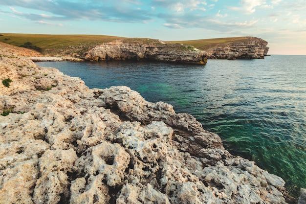 ビーチの崖の背景で青い海の上の澄んだ空