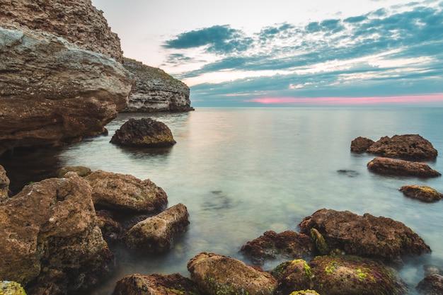 素晴らしい休暇先ビーチの日の出と海の崖の背景