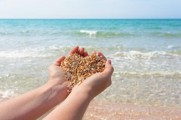 海岸でハート形の砂を手に