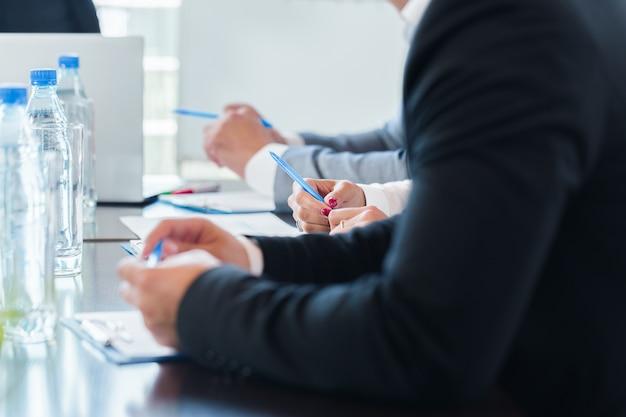 会議テーブルで一緒に働くビジネス人々