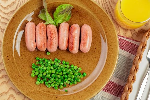 グリーンピースの朝食料理と揚げソーセージをクローズアップ