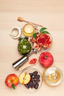 Мед, гранат, яблоко и даты на деревянной доске. еврейский новый год рош ха-шана