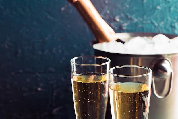 Бутылка шампанского в ведре со льдом и бокалами шампанского